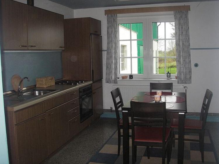 Küche mit Esstisch und vier Stühlen