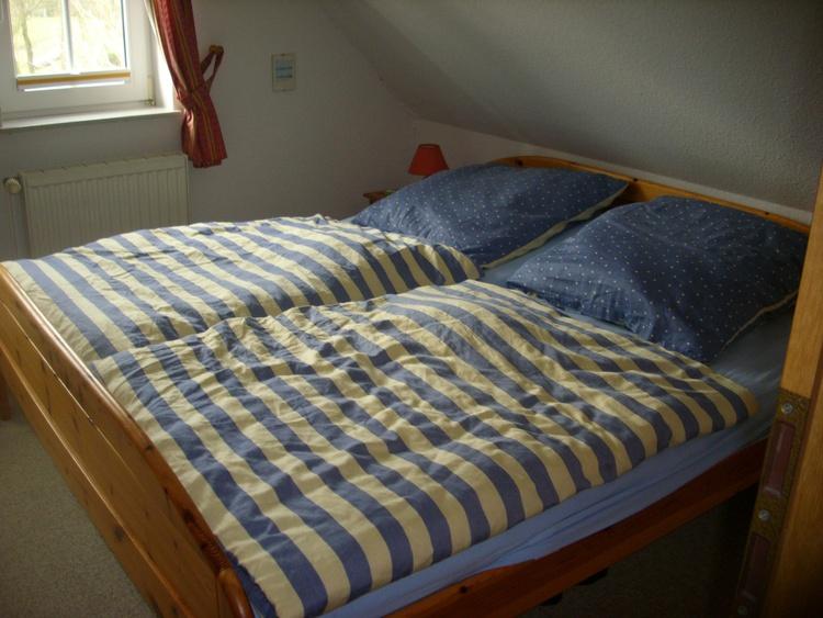 Einer der oberen Schlafräume mit Doppelbett, Schrank und Kinderbettchen