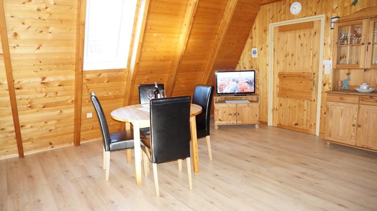 Wohnzimmer mit einer Essecke. Das Kiefernholz sorgt für eine behagliche Atmosphäre.
